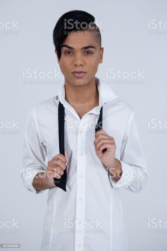 Portrait of confident transgender female holding tie royalty-free stock photo