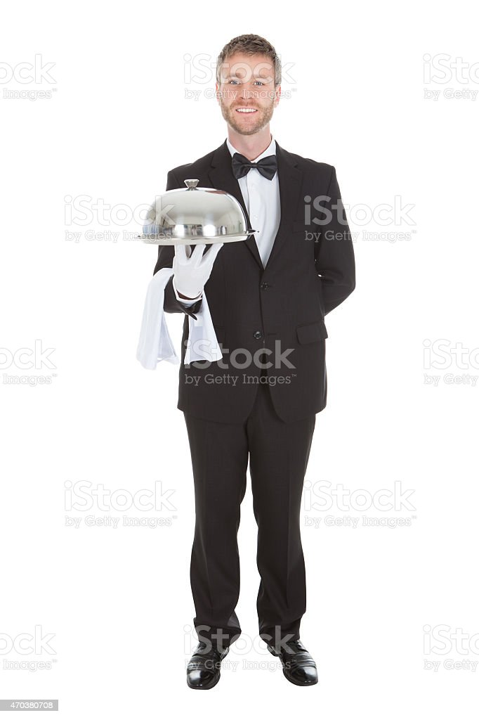 Portrait Of Confident Waiter Holding Domed Tray stock photo
