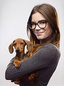 Portrait of confident young woman carrying dachshund. Smiling female is standing against white background. She is wearing eyeglasses and casuals. Vertical studio photography from a DSLR camera. Sharp focus on eyes.