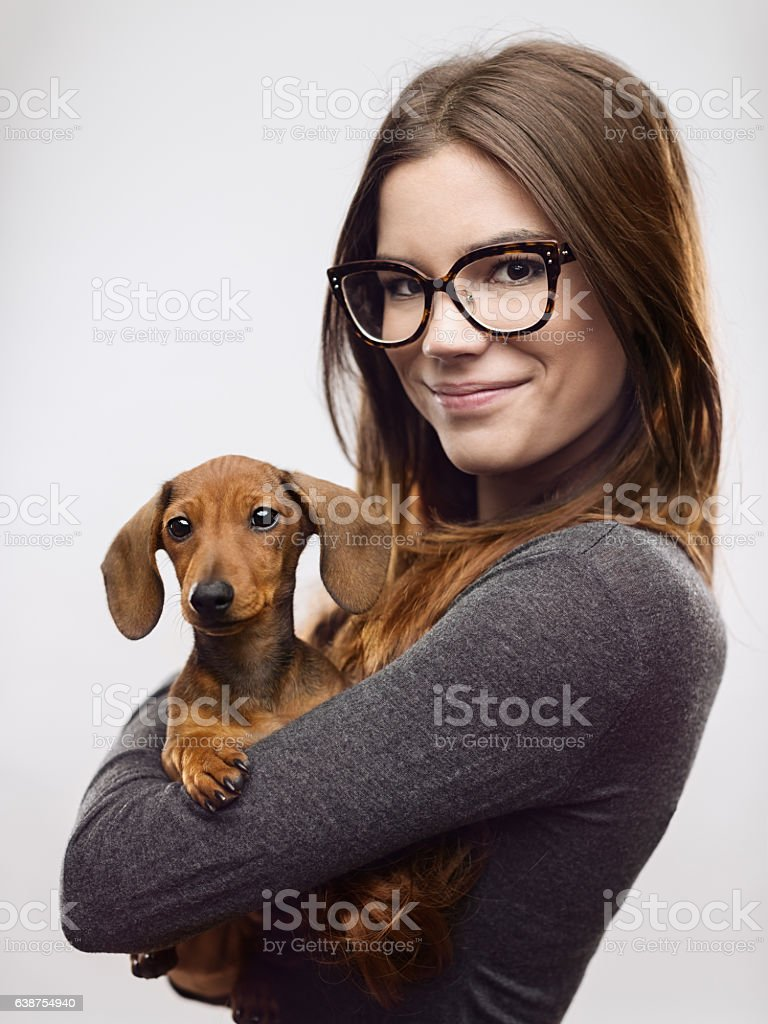 Portrait of confident woman carrying dachshund stock photo