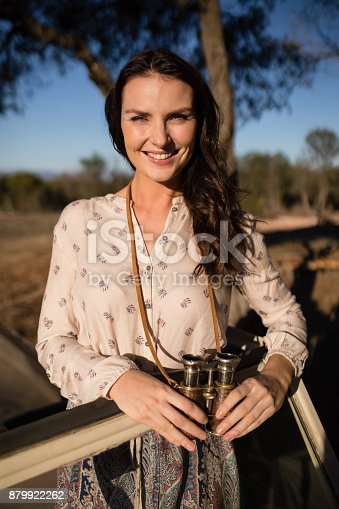Portrait of confident woman standing with binoculars in vehicle during safari vacation