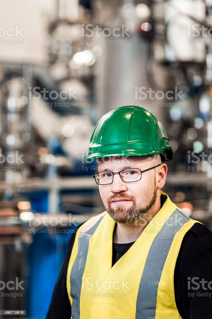 Portrait of confident worker standing in factory stock photo
