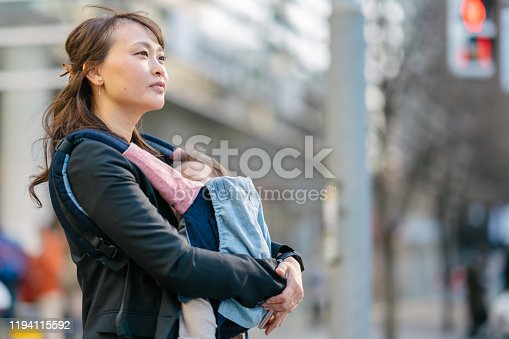 A portrait of a young confident working mother while commuting with her baby in the street.