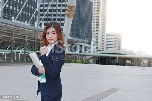 Portrait of confident young Asian business woman with ring binder standing at walkway of urban building background.