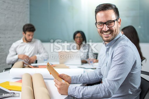 istock Portrait of confident young businessman analyzing paperwork and looking at camera in front of his business partners. 845520408