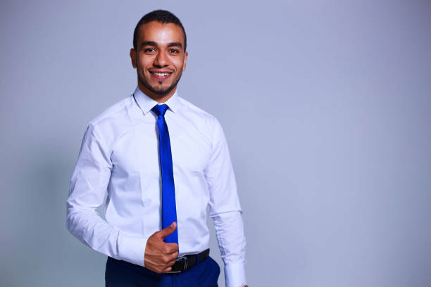 Portrait of confident young businessman standing on grey background. Business, people and office concept stock photo