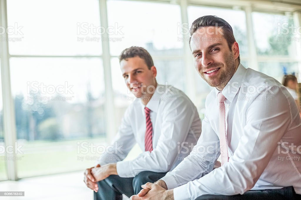 Portrait of confident young businessmen sitting in office stock photo
