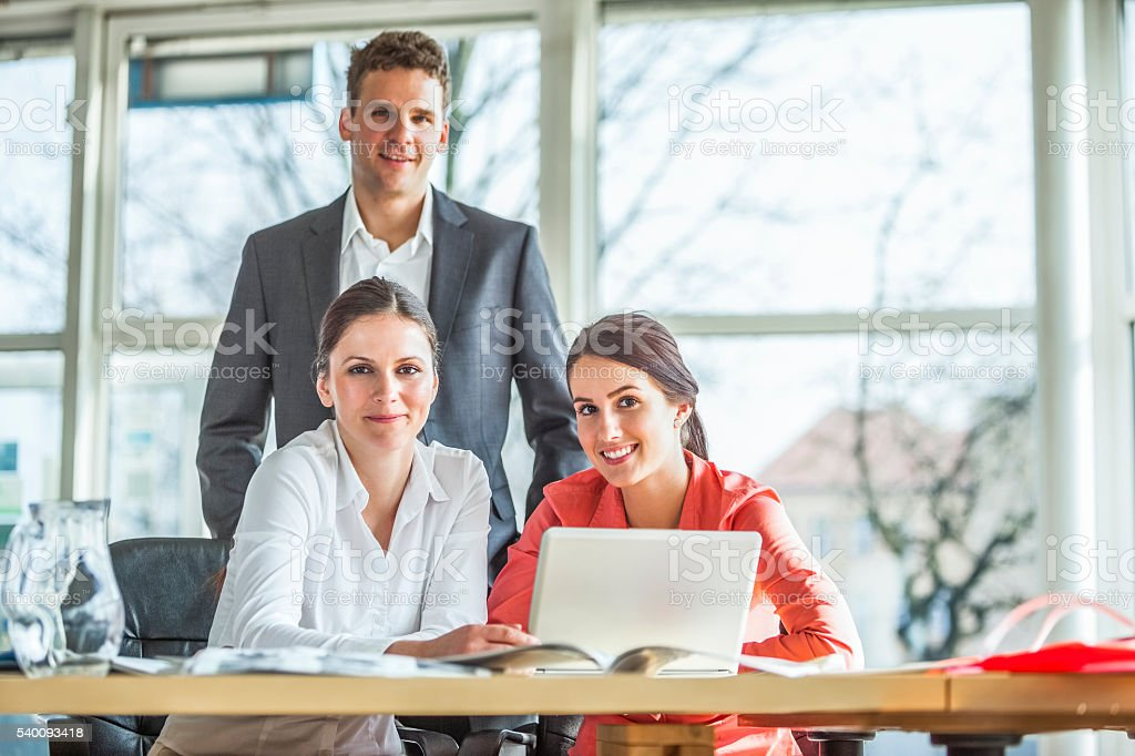 Portrait of confident young businesspeople at desk in office stock photo