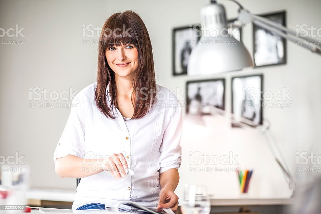 Portrait of confident young businesswoman analyzing brochure in creative office – Foto