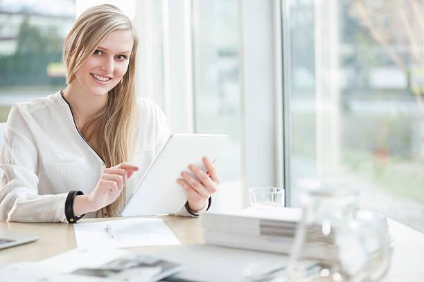 Porträt von überzeugter junger Geschäftsfrau am Schreibtisch – Foto