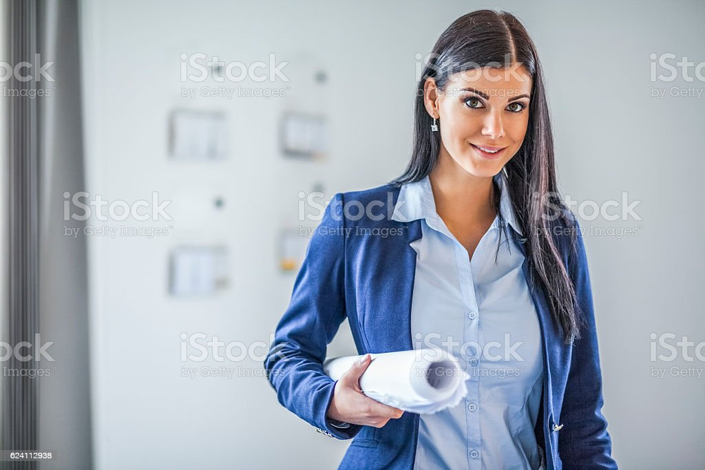 Portrait of confident young businesswoman holding blueprint in office stock photo