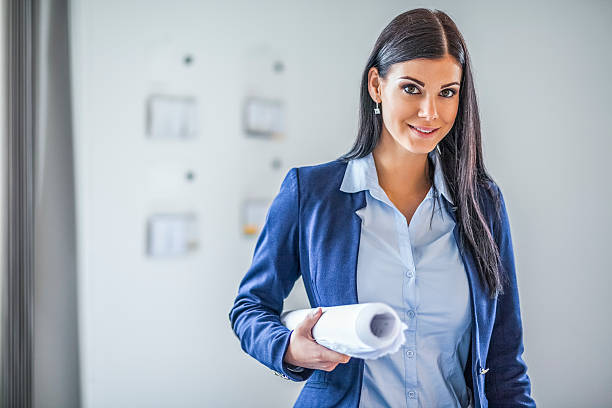 portrait of confident young businesswoman holding blueprint in office - architecte photos et images de collection