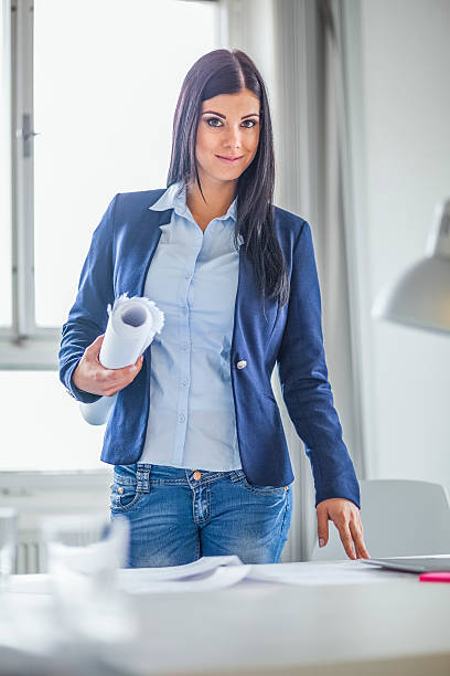 Portrait of confident young businesswoman holding blueprint in office – Foto
