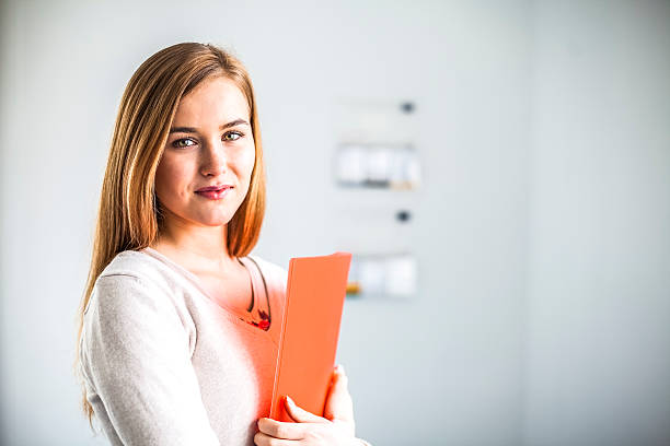 Portrait of confident young businesswoman holding file in office – Foto