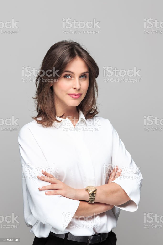 Portrait of confident young businesswoman Portrait of confident young businesswoman standing with hand crossed and looking at camera against grey background. 25-29 Years Stock Photo