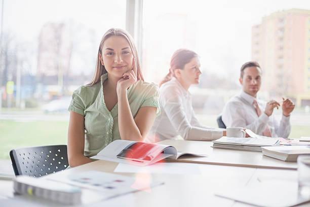 Porträt von zuversichtlicher junger Geschäftsfrau mit Kollegen im Meetingraum – Foto
