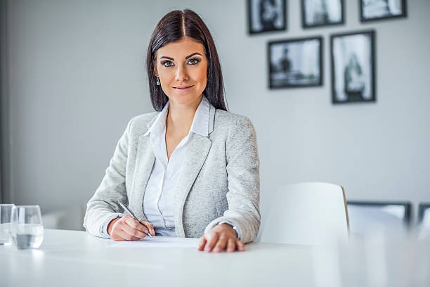 Portrait of confident young businesswoman writing on document in office – Foto