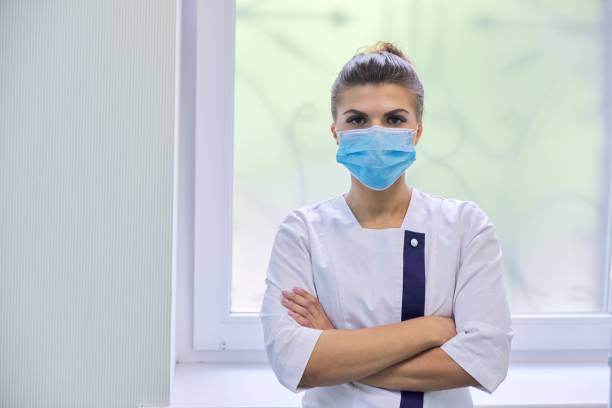Retrato de joven médica segura con máscara médica - foto de stock