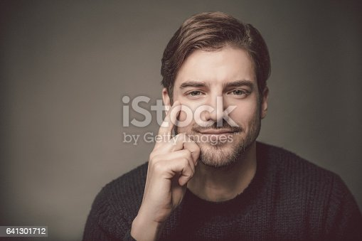 611630440 istock photo Portrait of confident young man with head in hand 641301712