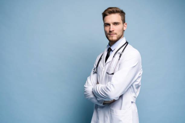 Porträt eines selbstbewussten jungen Arztes auf blauem Hintergrund. – Foto