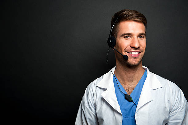 Portrait of confident young medical doctor on dark background stock photo