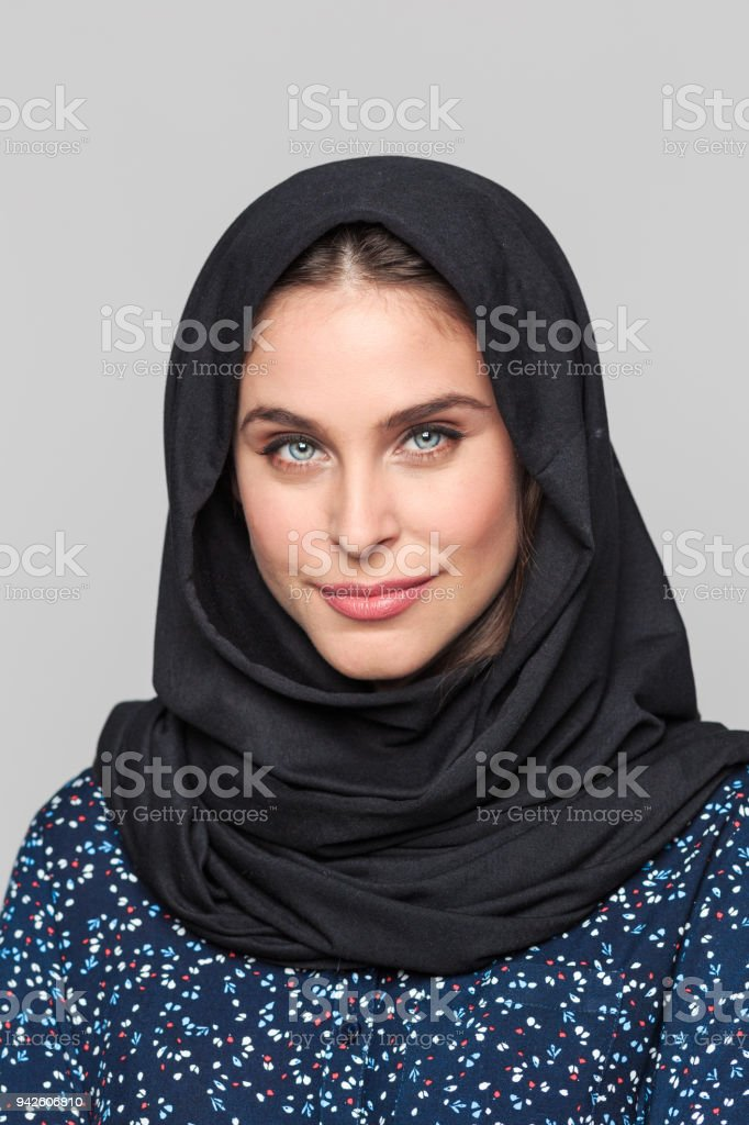 Portrait of confident young muslim woman Portrait of cheerful young muslim woman. Businesswoman in hijab looking at camera against grey background. 20-29 Years Stock Photo