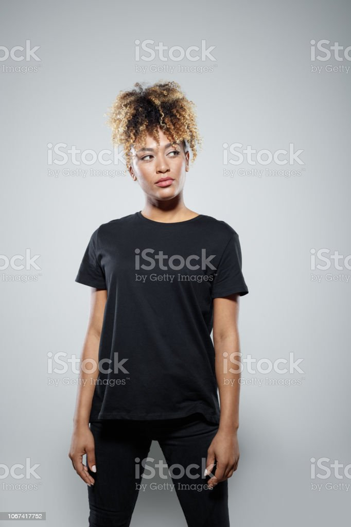 Portrait of confident young woman Strong young woman wearing black clothes, standing against grey background, looking away. Studio shot. Activist Stock Photo
