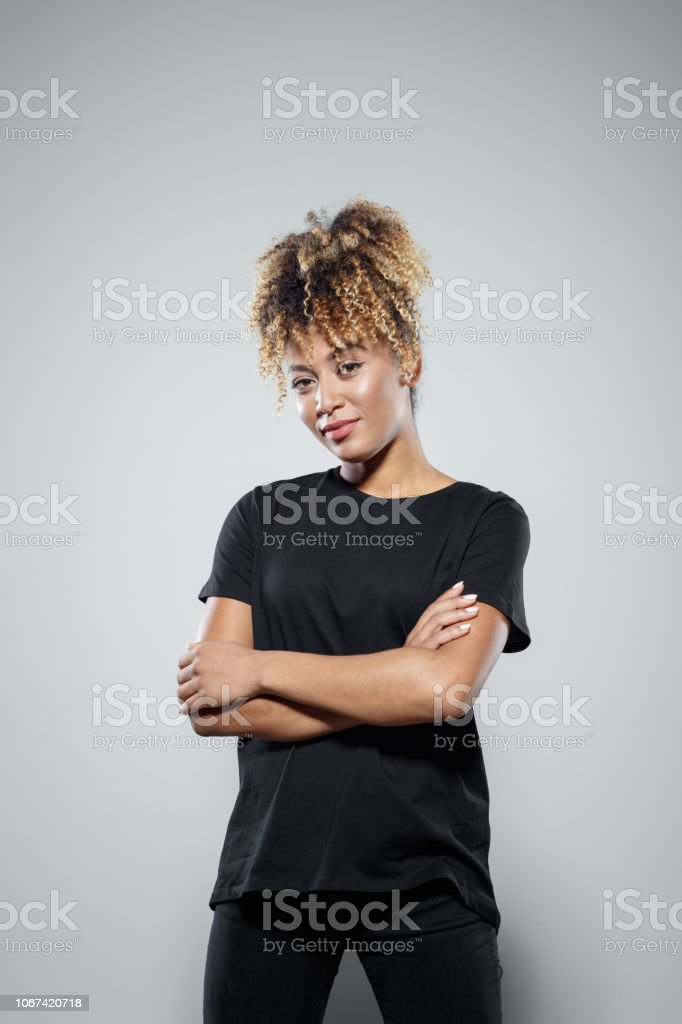 Portrait of confident young woman Strong young woman wearing black clothes, standing with arms crossed against grey background, smiling at camera. Studio shot. Activist Stock Photo
