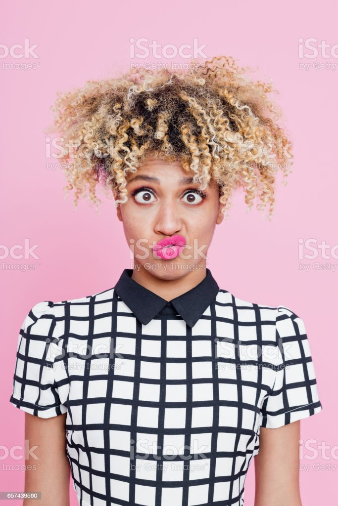 Portrait of confused afro american young woman making funny face Studio portrait of confused afro american young woman staring at the camera. Pink background. 20-24 Years Stock Photo