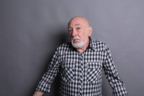 Portrait of confused senior man Portrait of unsure senior man looking confused, gray studio background raised eyebrows stock pictures, royalty-free photos & images