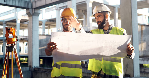 portrait of construction engineers working on building site - construction industry stock pictures, royalty-free photos & images