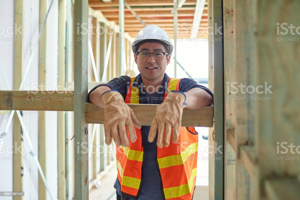 Portrait of construction worker by wooden planks stock photo