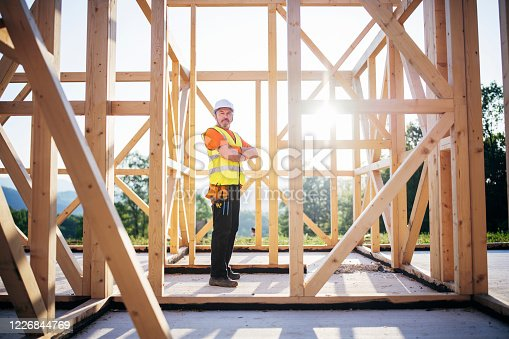 Full length portrait of manual worker in front of unfinished wooden construction building, arms crossed and looking at camera at sunset.