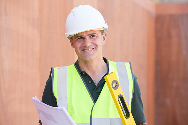 Portrait Of Construction Worker On Building Site With House Plan stock photo