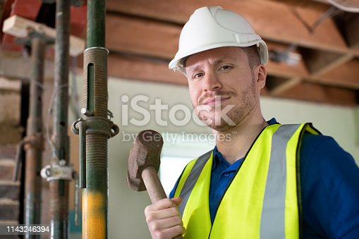 Portrait Of Construction Worker With Sledgehammer Demolishing Wall In Renovated House