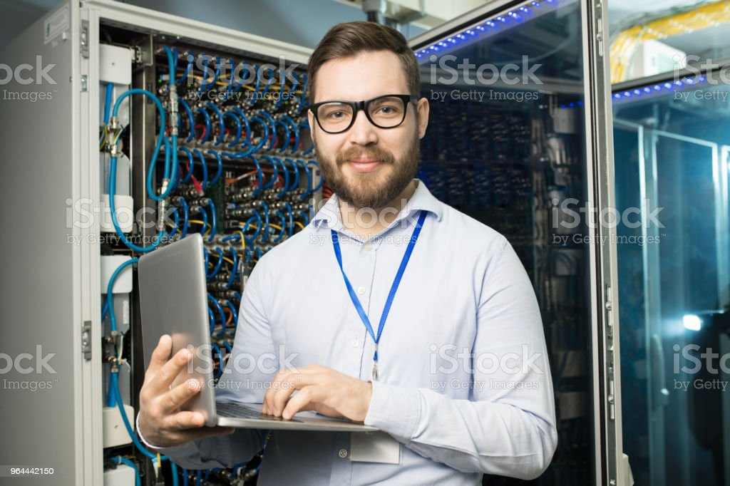 Portrait of content confident bearded highly professional IT engineer with badge on neck using laptop in network server room - Royalty-free Adult Stock Photo