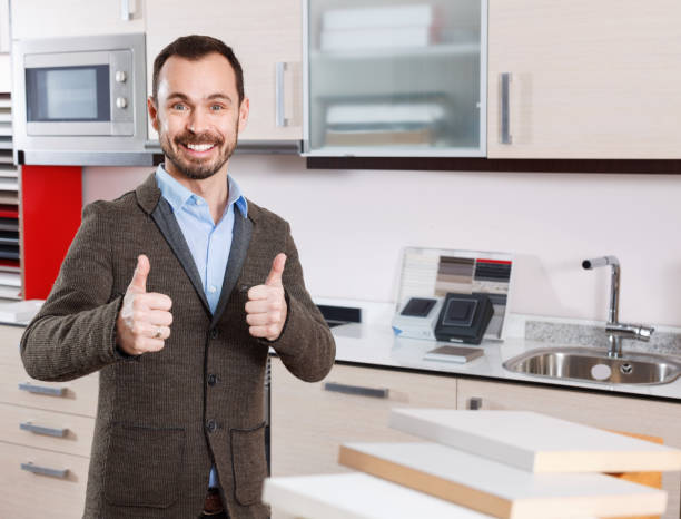 Portrait of contented bearded guy in kitchen furnishing store Portrait of contented bearded  cheerful positive guy in kitchen furnishing store approbation stock pictures, royalty-free photos & images