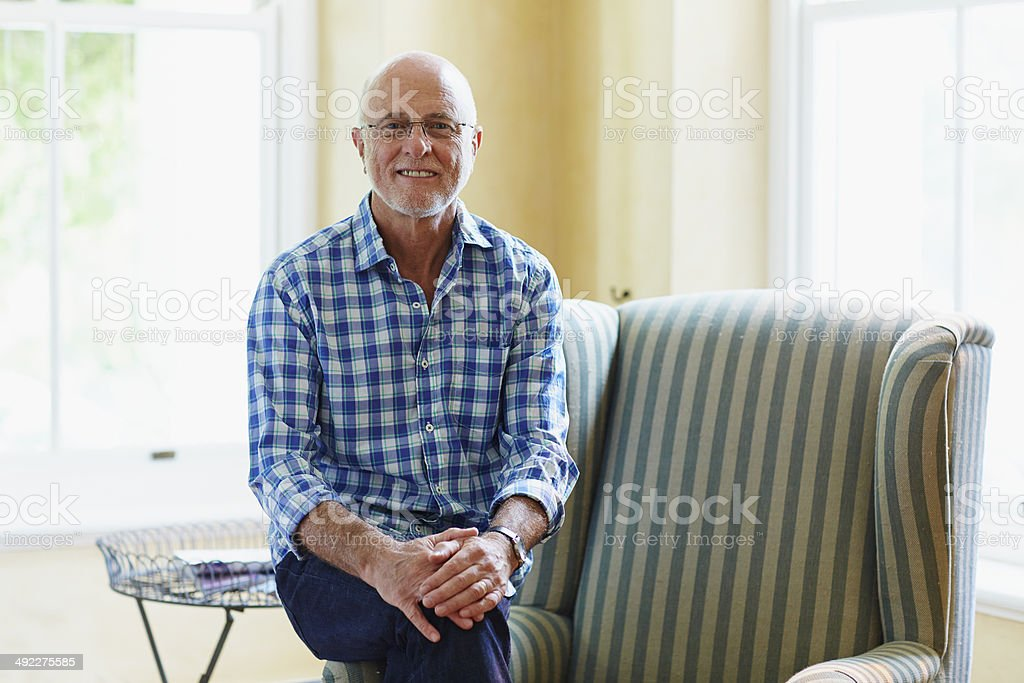 Portrait of contented senior man at home stock photo