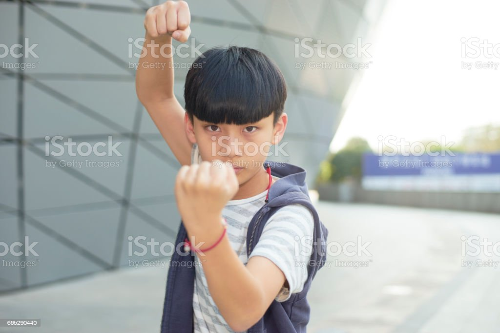 portrait of cool Asian kid posing outdoors stock photo