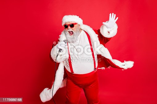 istock Portrait of cool funny fat overweight santa claus with big belly sing song on christmas party wear style stylish trendy eyeglasses eyewear hat isolated over red background 1175686168
