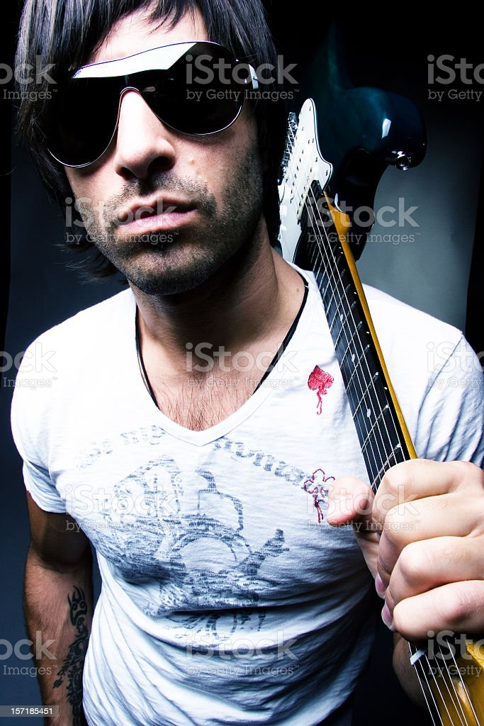 Portrait of cool rock star with sunglasses holding guitar stock photo