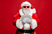 istock Portrait of cool stylish elderly santa claus hipster millionaire have cash, want buy presents spend on winter season sales discount wear cap hat eyewear eyeglasses isolated over red background 1180383303
