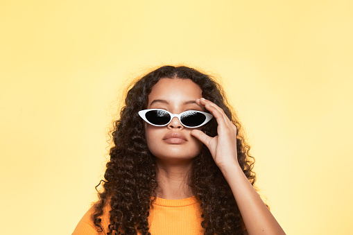 A portrait of a beautiful teenager with white sunglasses, isolated on yellow studio background