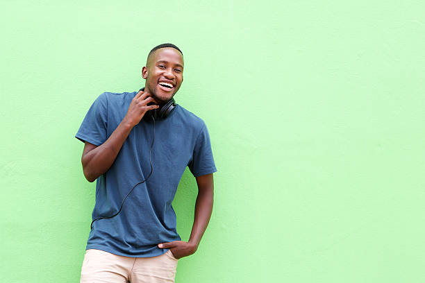 Portrait of cool young african guy Portrait of cool young african guy standing against a green wall only young men stock pictures, royalty-free photos & images