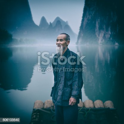 Portrait of a River Lee Cormorant Fisherman standing on a raft, with karst mountains in the background. Guangxi Region of China.