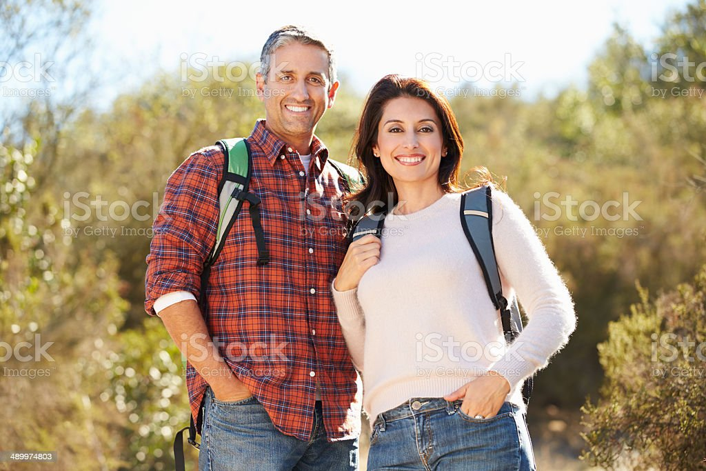 Portrait Of Couple Hiking In Countryside Wearing Backpacks stock photo