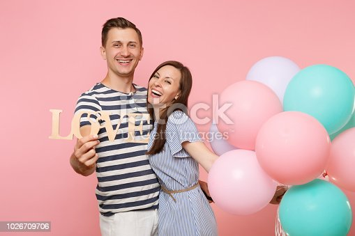 istock Portrait of couple hold wooden word letters love. Woman and man in blue clothes celebrating birthday holiday party on pastel pink background with colorful air balloons. People sincere emotions concept 1026709706