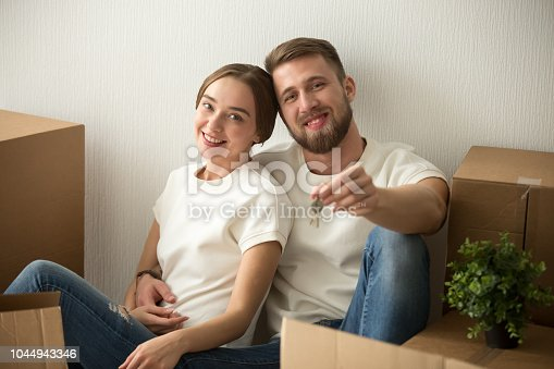 938682826istockphoto Portrait of couple holding keys excited to move in together 1044943346