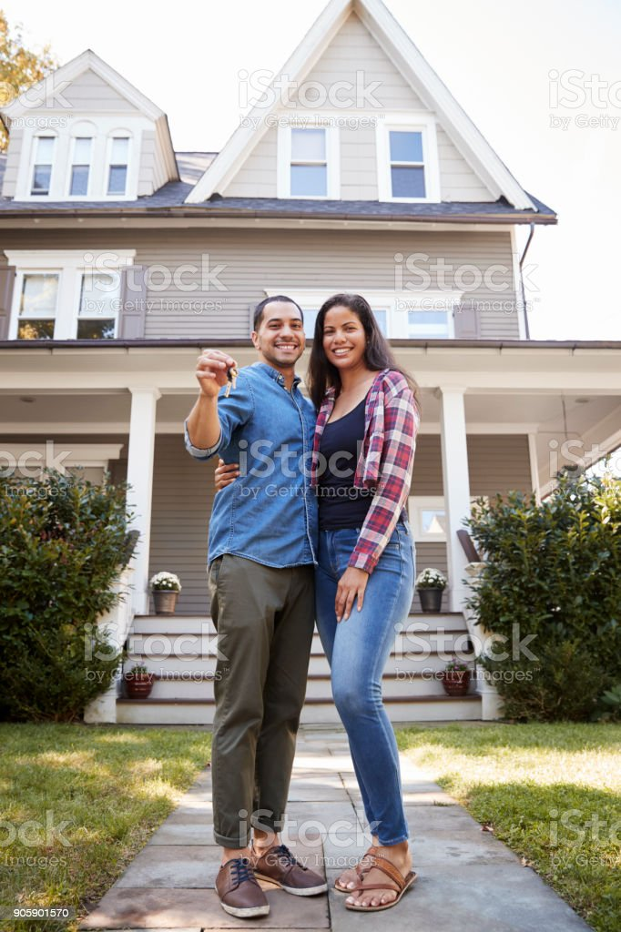 Portrait Of Couple Holding Keys To New Home On Moving In Day stock photo