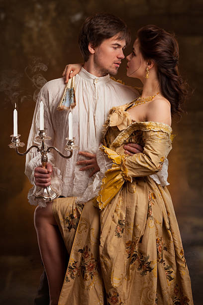 portrait of couple in historical costumes on dark background stock photo